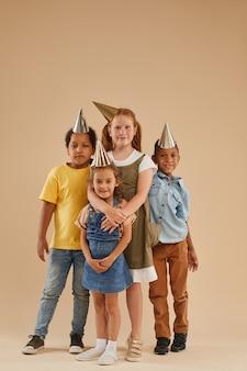 Portrait de pleine longueur verticale d'un groupe diversifié d'enfants portant des chapeaux de fête posant sur beige