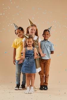 Portrait de pleine longueur verticale d'un groupe diversifié d'enfants portant des chapeaux de fête tout en posant sous éclat de confettis colorés