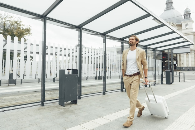 Portrait de pleine longueur de voyageur masculin portant un costume élégant marchant sur la gare publique avec valise blanche