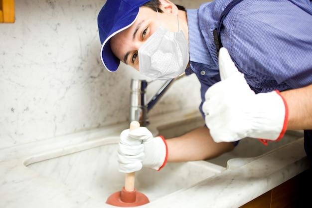 Portrait d'un plombier souriant utilisant un concept de piston, de covid ou de coronavirus