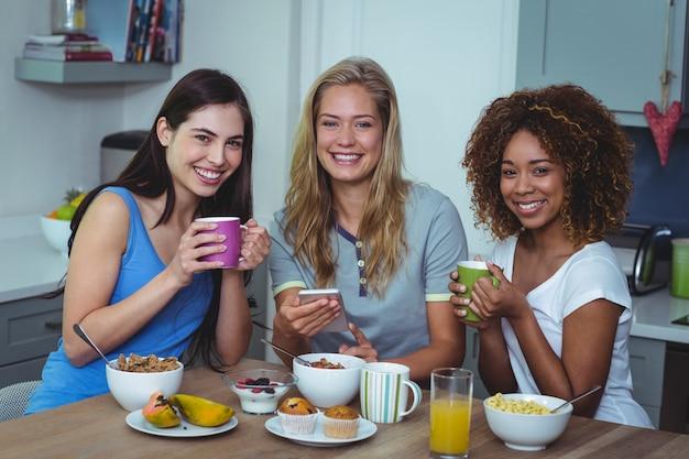 Portrait de plusieurs amis ethniques ayant un café à la table