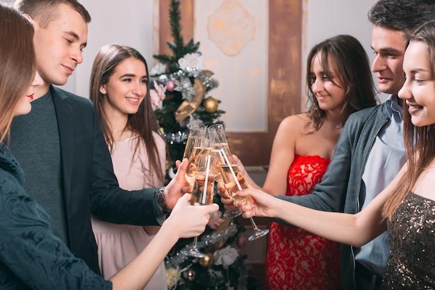 Portrait de plusieurs amis portant un toast à noël
