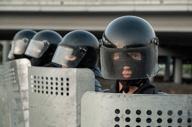 Portrait d'un policier sérieux en tenue de protection tenant un bouclier anti-émeute et debout contre une rangée de collègues