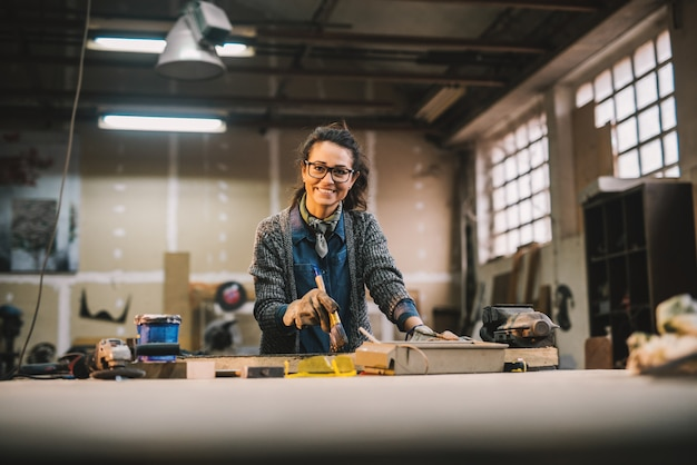Portrait portrait of happy attractive female female worker painting wood with black color in the sunny workshop