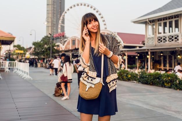 Portrait positif d'été de femme joyeuse en tenue élégante parlant par téléphone mobile et souriant sur riverfront à bangkok