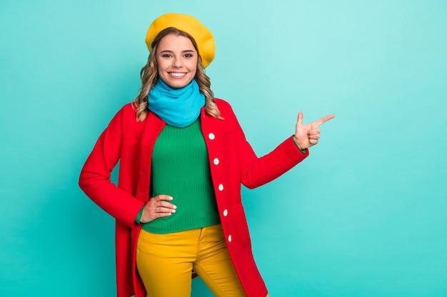Portrait positif gai fille douce promoteur pointer l'index copyspace recommander suggère de sélectionner des annonces promo porter bon look pull pantalon pantalon isolé fond de couleur turquoise