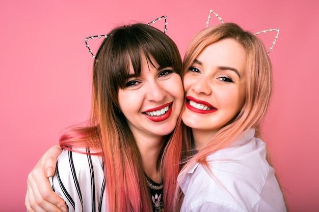 Portrait positif mignon d'heureux joli meilleur ami soeur femmes câlins souriant, poils roses à la mode, oreilles de chat de fête, look familial