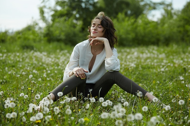 Portrait de printemps d'une femme assise dans un champ sur l'herbe parmi les fleurs de pissenlit. femme joyeuse aime le temps de printemps ensoleillé. beauté naturelle d'une femme, cosmétiques naturels