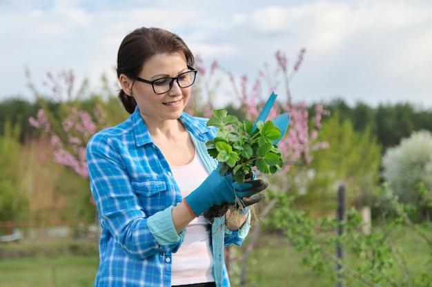 Portrait de printemps d'une femme mature dans le jardin avec des outils, des arbustes à la fraise.