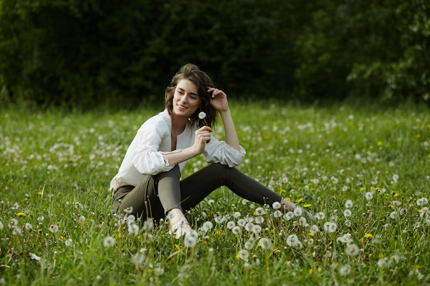 Portrait de printemps d'une fille assise dans un champ sur l'herbe parmi les fleurs de pissenlit