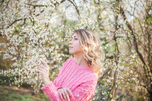 Portrait de printemps d'une jeune blonde près d'un arbre en fleurs. heureuse jeune femme. printemps.