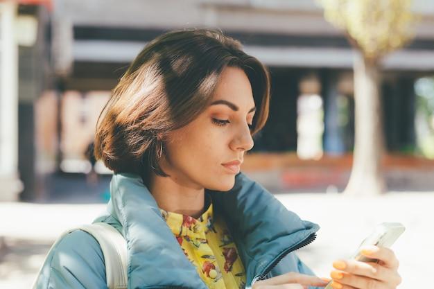 Portrait de printemps en plein air de femme caucasienne regarde sur l'écran du téléphone avec un visage sérieux