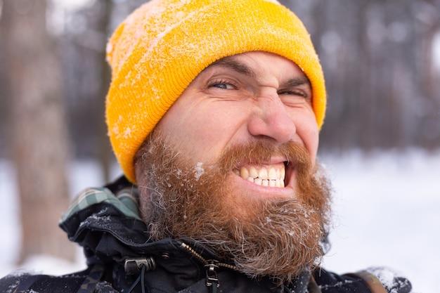 Un portrait proche d'un homme avec une barbe, tout le visage dans la neige, dans une forêt enneigée