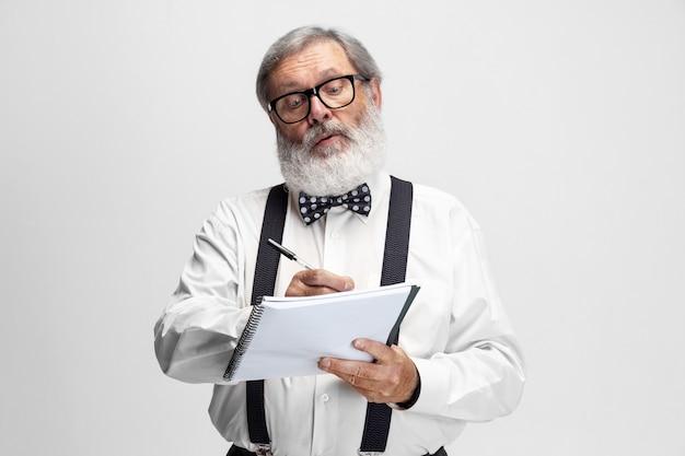 Portrait de professeur d'homme aîné posant isolé sur blanc