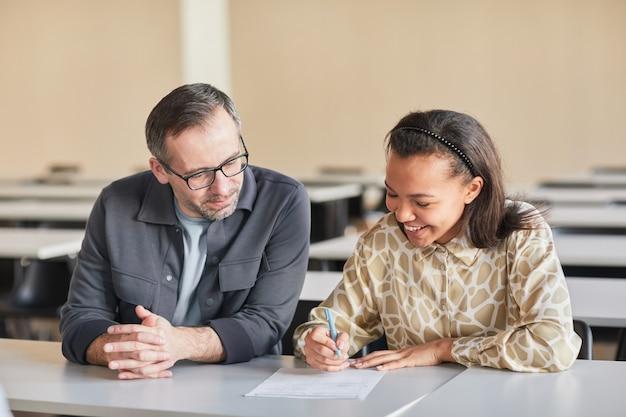Portrait d'un professeur mature souriant aidant une jeune femme afro-américaine qui étudie dans l'auditorium du collège, espace pour copie