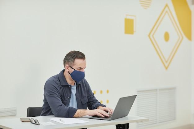 Portrait d'un professeur d'université mature portant un masque tout en utilisant un ordinateur portable dans un auditorium d'école moderne, espace de copie