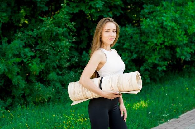 Portrait de professeur de yoga excité posant avec tapis de fitness, entraîneur de fitness heureux ou entraîneur dans l'entraînement de sports de plein air