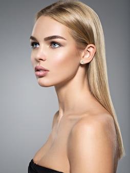 Portrait de profil d'une belle jeune femme aux longs cheveux raides et légers.
