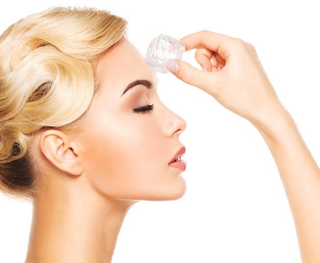 Portrait de profil de la belle jeune femme aux yeux fermés applique la glace sur le visage. isolé sur blanc.