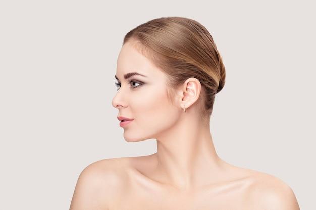 Portrait de profil de la belle jeune femme blonde aux yeux verts sur fond gris agrandi. fille avec une peau propre