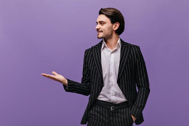 Portrait de profil d'une charmante jeune brune en chemise légère classique et costume rayé noir, regardant de côté et pointant sur l'espace libre d'une main