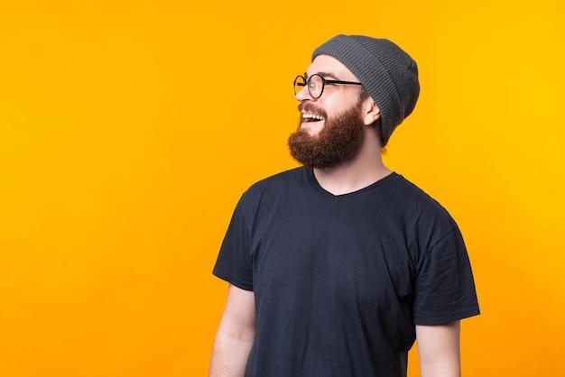 Un portrait de profil de côté d'un homme barbu avec des lunettes à la recherche et au sourire