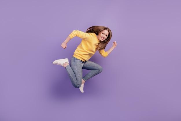 Portrait de profil d'une dame active folle et joyeuse qui saute la saison des ventes pressées sur fond violet