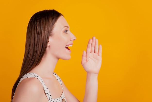 Portrait de profil de la dame de l'annonceur du promoteur regarde l'espace vide crier la bouche ouverte sur fond jaune