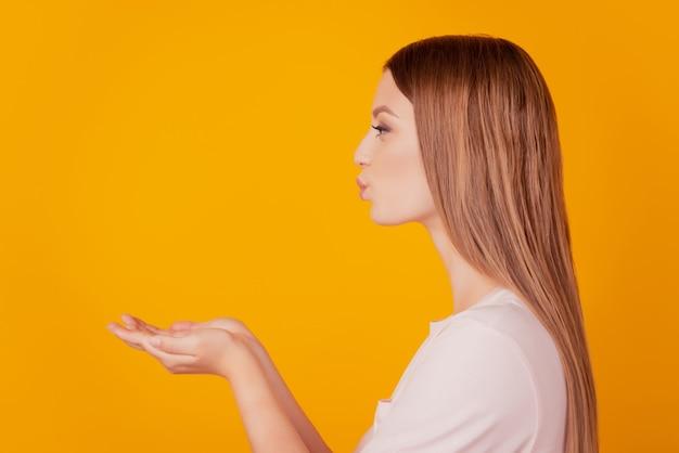 Portrait de profil d'une dame blonde tentante et douce qui regarde l'espace vide tenir les paumes souffler un baiser d'air sur fond jaune