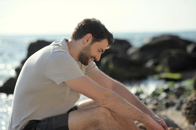 Portrait de profil extérieur jeune homme élégant, polo blanc, assis sur une pierre
