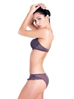 Portrait de profil d'une femme avec un beau corps parfait mince en bikini blanc isolé
