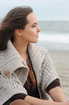 Portrait de profil de femme calme assis seul sur une plage de la mer