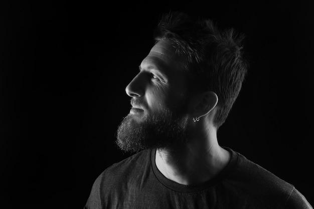 Portrait de profil d'un homme sur fond noir, noir et blanc