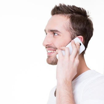 Portrait de profil d'homme heureux appelant par mobile dans les occasionnels - isolé sur blanc. communication conceptuelle.