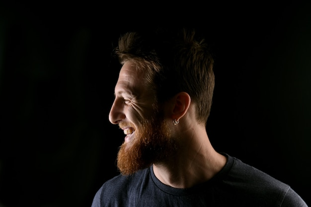 Portrait de profil d'un homme souriant sur fond noir