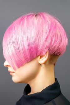Portrait de profil d'une jeune femme de race blanche avec coupe de cheveux bob rose isolé sur fond gris