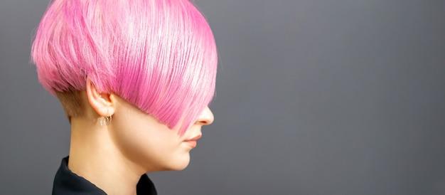 Portrait de profil d'une jeune femme de race blanche avec une coupe de cheveux rose isolée sur fond gris, espace de copie.