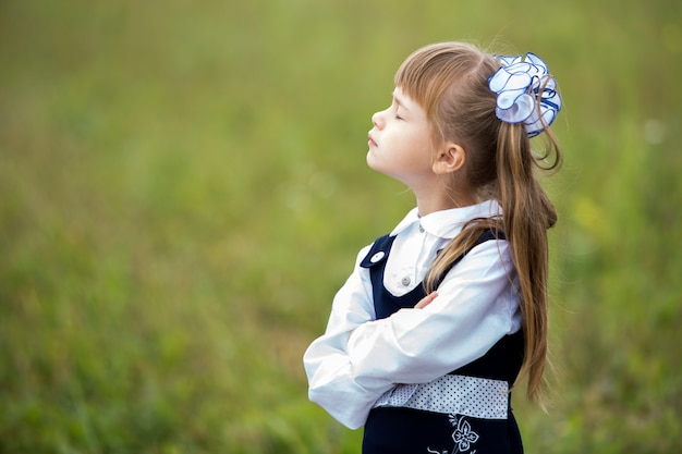 Portrait de profil de la jolie fille adorable de première niveleuse en uniforme d'école et blanche s'incline dans les cheveux longs avec tête haute et les yeux fermés.