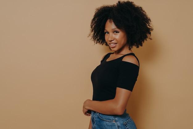 Portrait de profil d'une jolie fille afro-américaine magnifique avec un sourire rayonnant et des lèvres pleines en tenue décontractée isolée sur fond beige foncé avec espace de copie pour la publicité, concept d'émotions positives