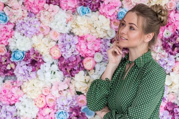 Portrait de profil d'une jolie fille blonde sur un fond floral