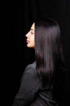 Portrait de profil d'une jolie fille magnifique avec un sourire radieux lèvres charnues en tenue décontractée sur fond noir avec espace copie espace vide.