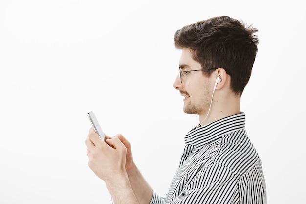 Portrait de profil de joyeux modèle masculin attrayant insouciant dans des verres et chemise rayée, tenant un smartphone tout en discutant avec des amis et en écoutant de la musique dans des écouteurs