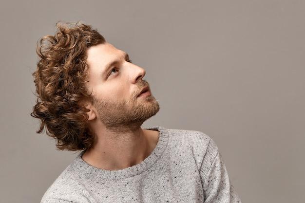 Portrait de profil de magnifique beau jeune homme avec des traits parfaits, des poils et des cheveux rougeâtres posant au mur de fond blanc en cavalier, regardant avec une expression faciale rêveuse