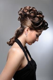 Portrait de profil d'un modèle féminin avec une belle coiffure de mariage.