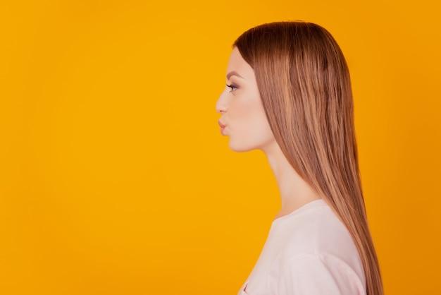 Portrait de profil d'une tendre dame affectueuse regarde les lèvres de l'espace vide envoient un baiser d'air sur fond jaune