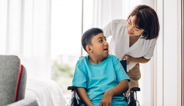 Portrait de profiter de l'amour heureux famille mère asiatique jouant et aidant aidant à regarder l'enfant handicapé fils assis dans des moments en fauteuil roulant bon moment à la maison. concept de soins aux personnes handicapées