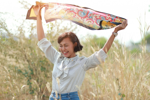Portrait de profiter ou heureux femme avec tissu dans le fond de la nature.