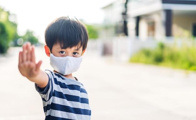 Portrait de profiter d'un petit garçon asiatique heureux portant un masque de protection pour la quarantaine pour le coronavirus avec distanciation sociale avant de quitter la maison