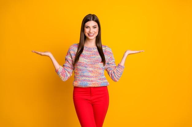 Portrait de promoteur de fille cool confiant positif tenir main présente décision de choix conseiller recommander des annonces promo suggérer sélectionner porter pull de style décontracté isolé sur couleur vive
