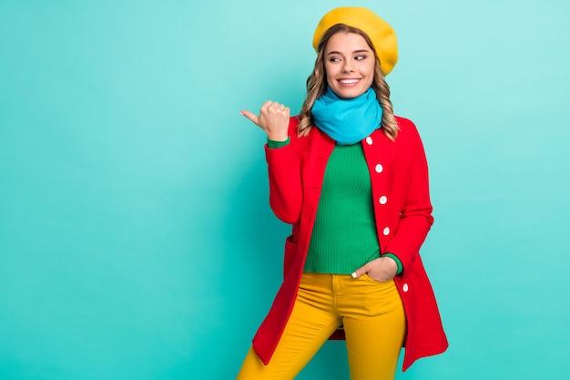 Portrait de promoteur fille joyeuse positive pointer le doigt du pouce copyspace afficher une publicité promo porter des pantalons pantalons isolés sur fond de couleur sarcelle